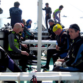 The boat crew help the divers gear-up